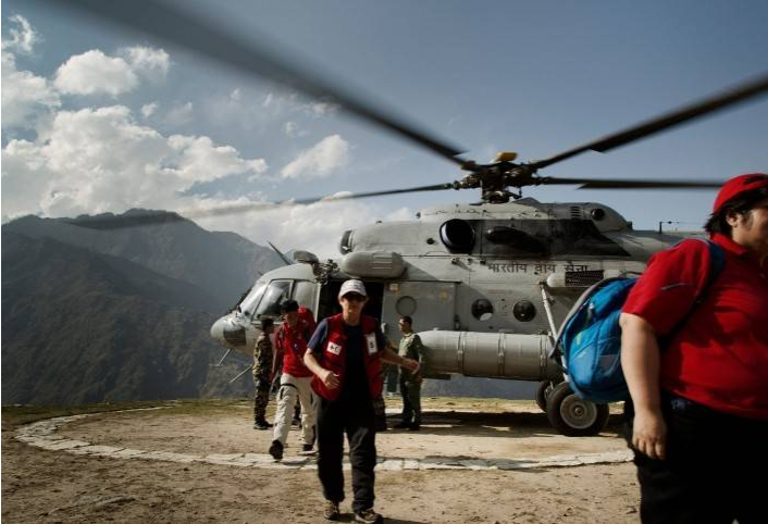 Red Cross volunteers getting off a helicopter